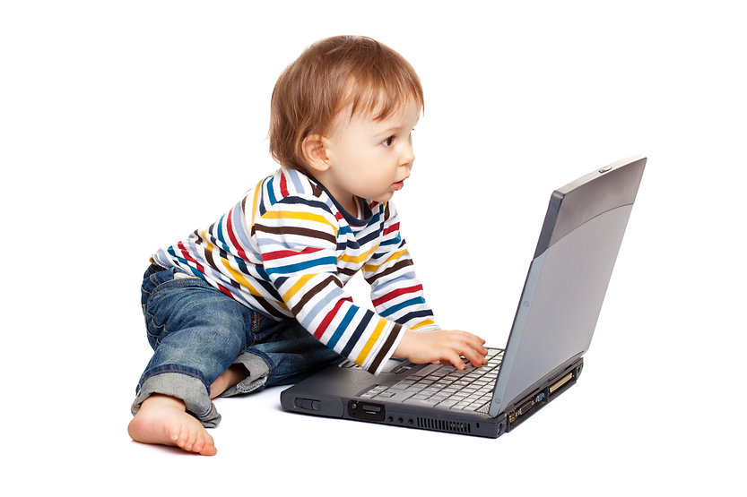 Adorable one year old child using laptop