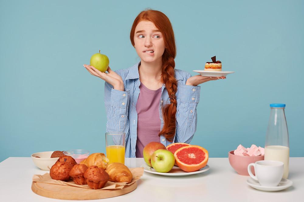 Menina indecisa na escolha entre alimentos saudáveis e alimentos industrializados.
