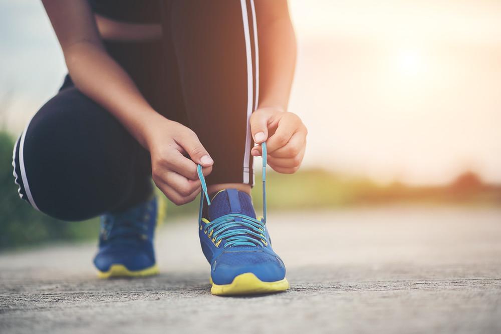 moça se preparando para fazer atividade física. Amarrando o tênis.
