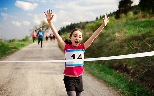 Small girl runner crossing finish line in a race competition in nature..jpg