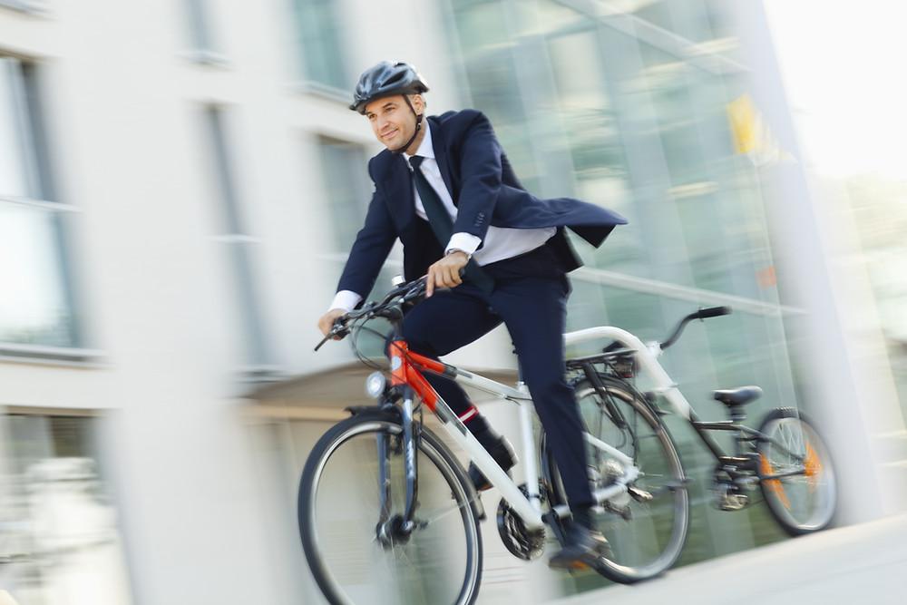 Homme en costume qui se rend au travail avec son vélo