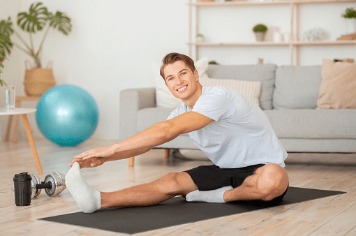 Indoor weight training for beginners man exercising sitting on a yoga mat and a cough in the background