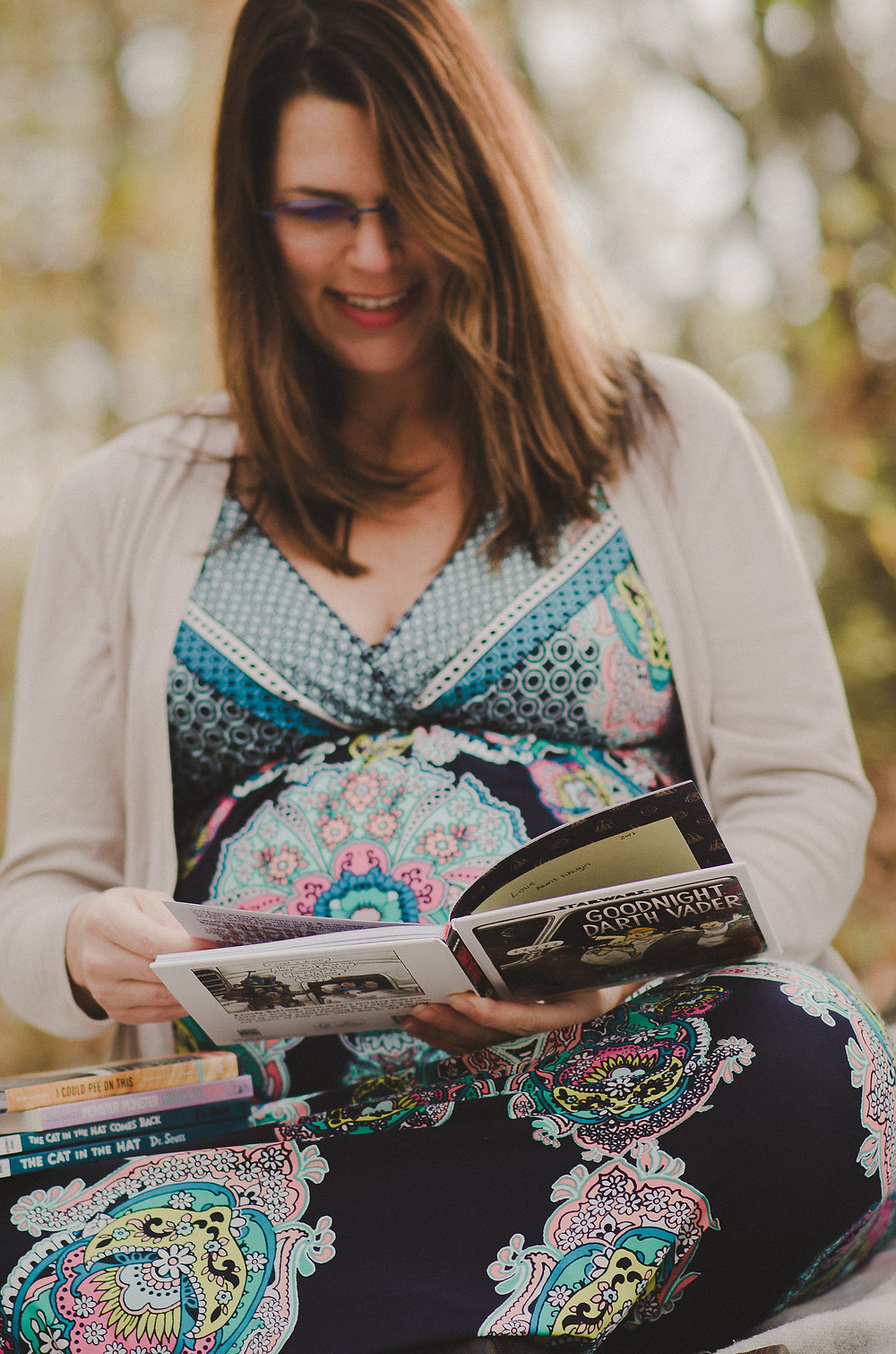 "Pregnant mom of twins reading ""Goodnight Darth Vader"" during her maternity session"