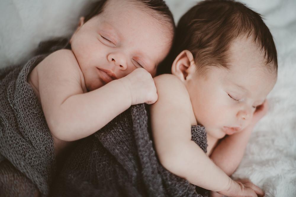 newborn twin girl hugs her twin brother