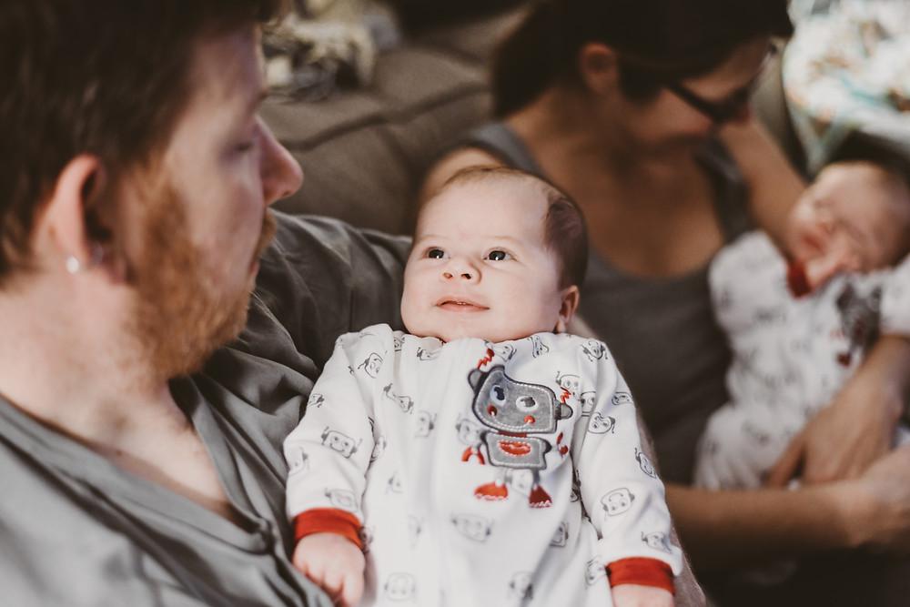 newborn baby boy smiling at dad