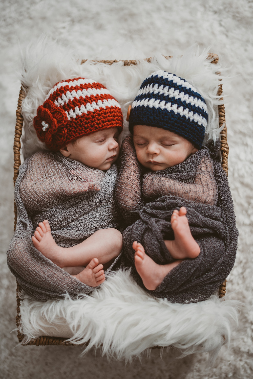 Newborn baby twins sleeping in basket with hand knit hats, one with a button and the other with a knit flower