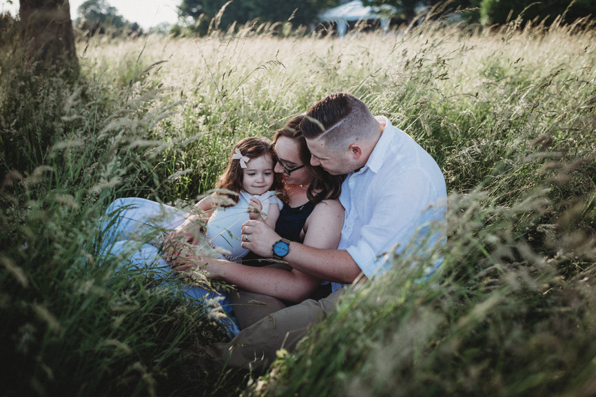 Family sitting in tall grass at sunset f