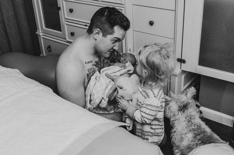 Father holding newborn son after homebir