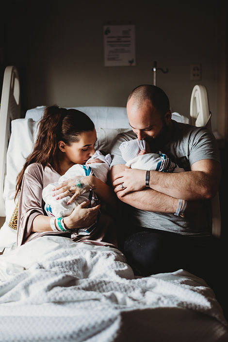 Parents kissing newborn baby twins in Backus Hospital Norwich Connecticut