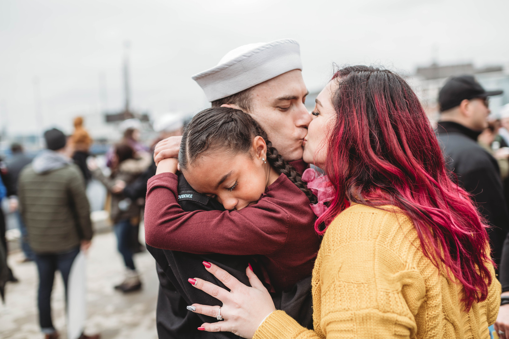 Couple kissing on pier after long deployment