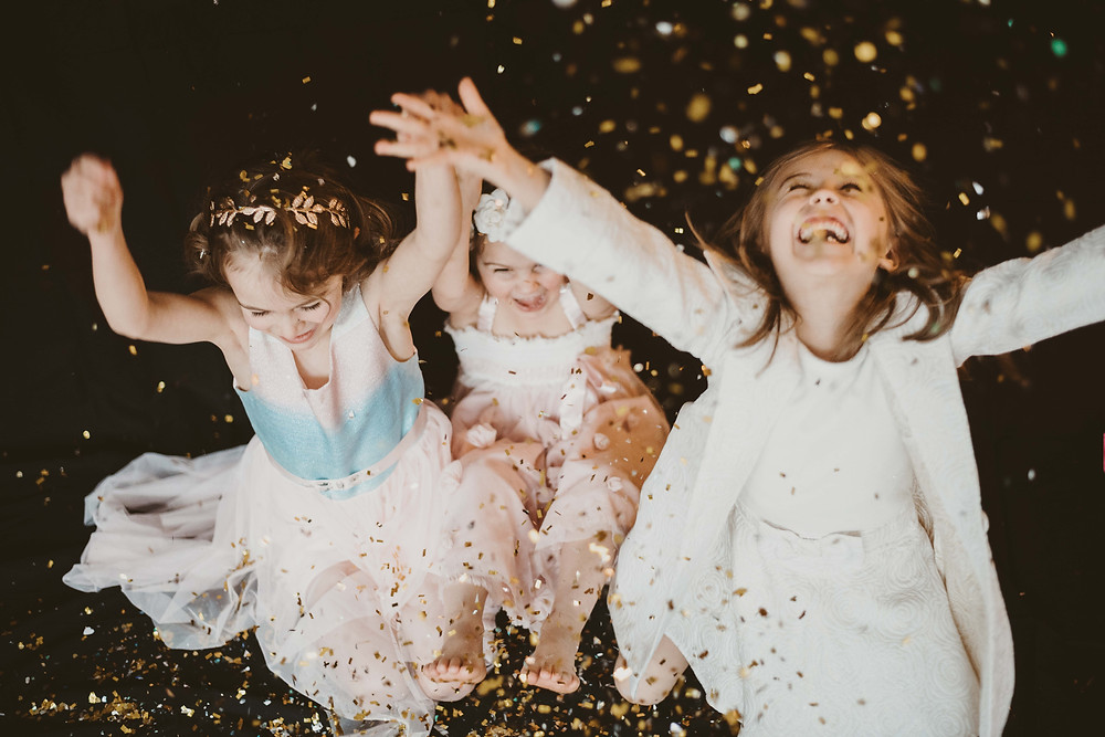 Three little girls throwing glitter at glitter mini photo session. Best studio photographer in Norwich, Connecticut