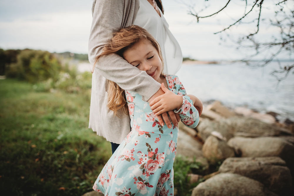 Daughter snuggled against mom in flowy white shirt during family session on the waterfront on Southeast Connecticut Coast
