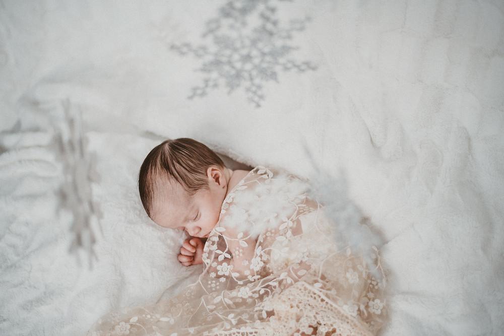 Newborn baby lies on white blanket under snowflakes