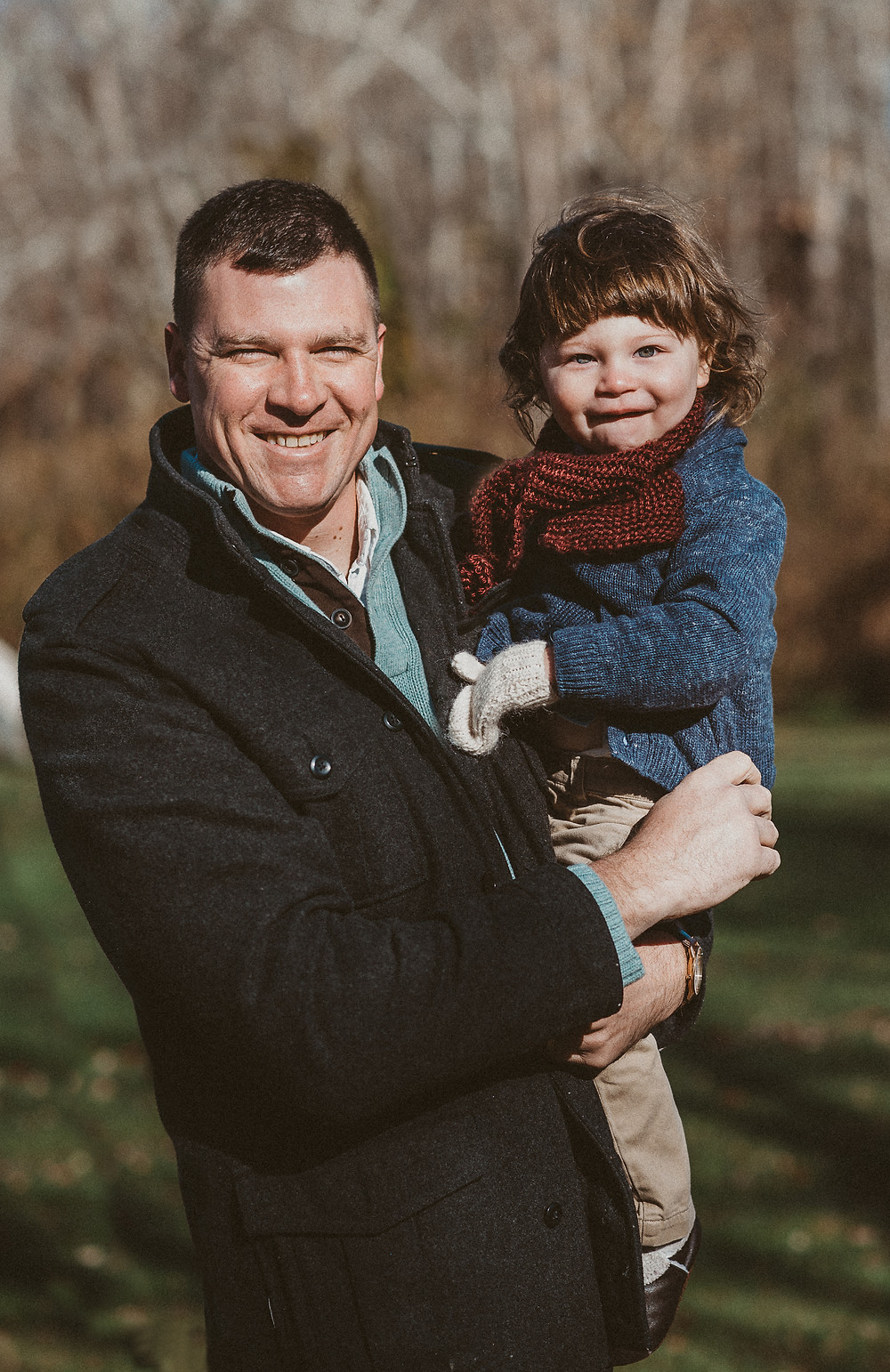 Father holding son smiling at the New London CT family photographer