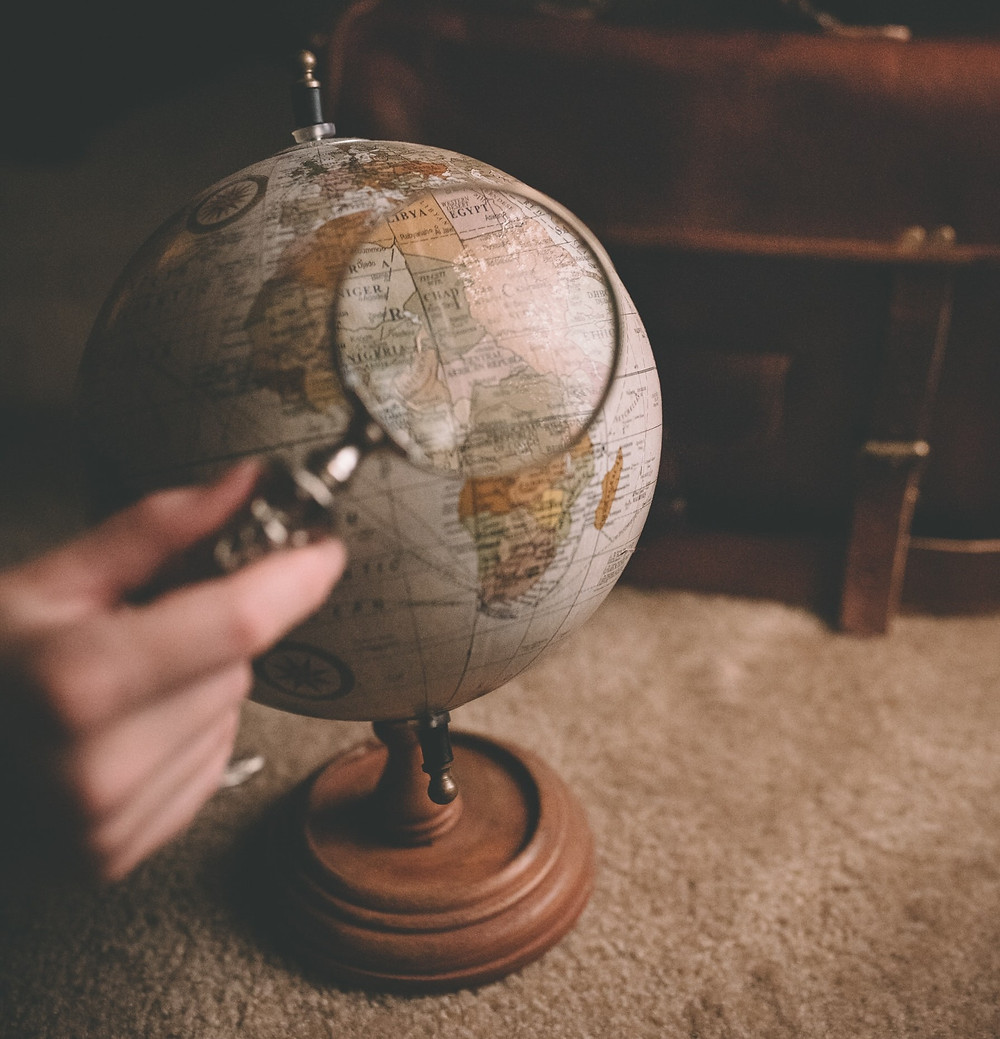 A hand with a magnifying glass looking at a specific country/continent on a globe.