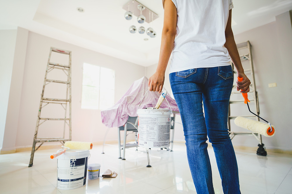 A woman standing in a room ready to paint