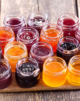 various jars of fruit jam on wooden tabl
