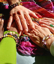 5 hands meet on a colorful scarf wearing bracelts made by Gina Rose Halpern.