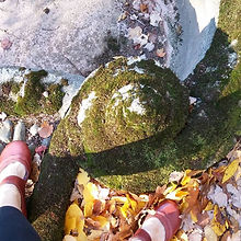 My feet with a moss covered spiral garden form.