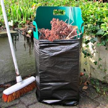 Imagen de uso de una lámina Pack-Bag, manteniendo abierta una bolsa para recoger hojas en el jardín