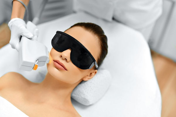 Happy woman receiving IPL skin rejuvenation treatment to her face