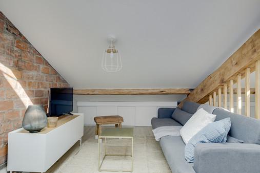 Salon mur briques scandinave table basse dorée claustra tasseaux