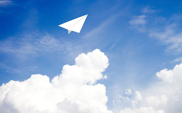 写真:青空を飛んでいく白い紙飛行機