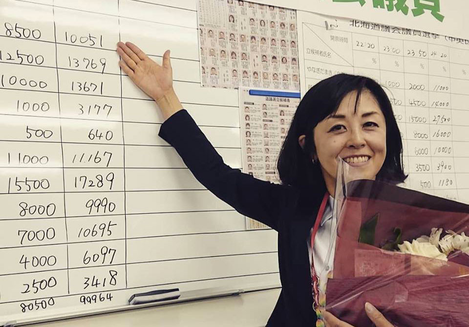 写真:得票数を記入したボードの前で