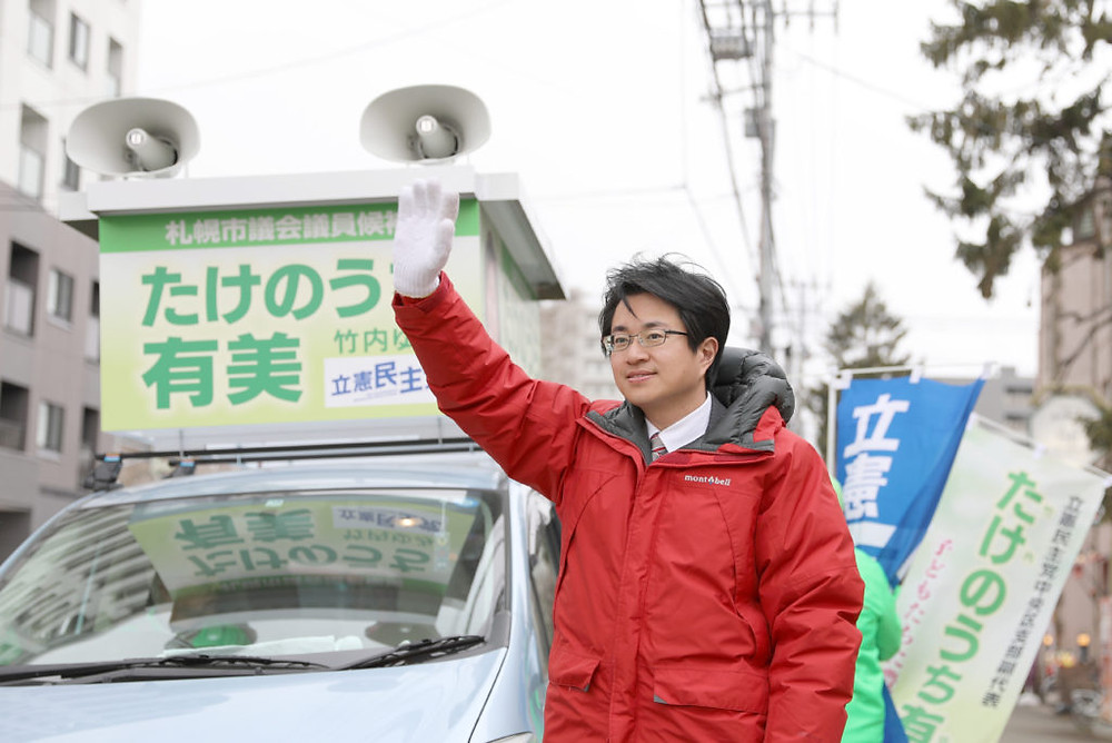 写真:街頭で手を振る道下衆議院議員