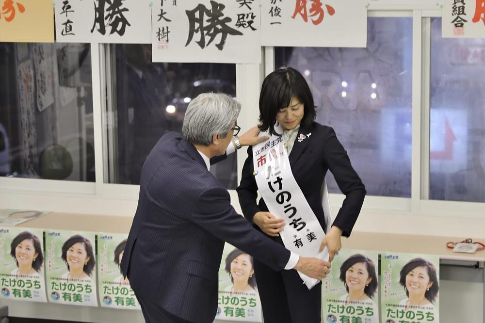 写真:長谷川まもる市議会議員にたすきをかけていただく