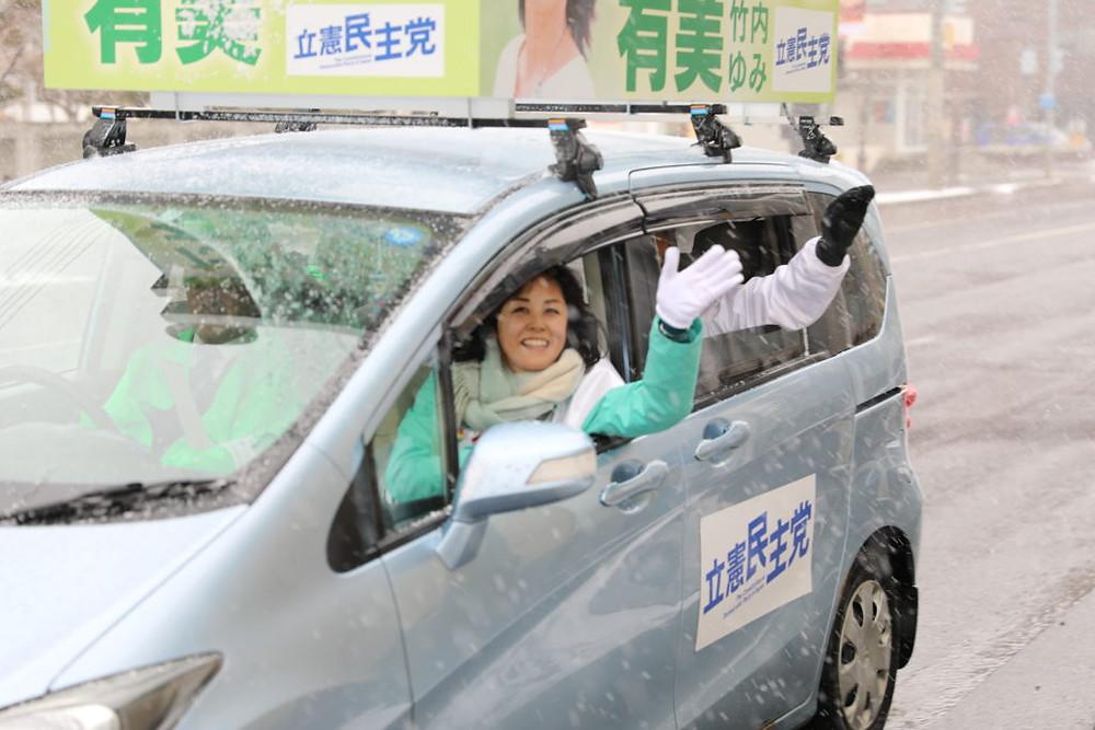 写真:車から手を振るたけのうち有美