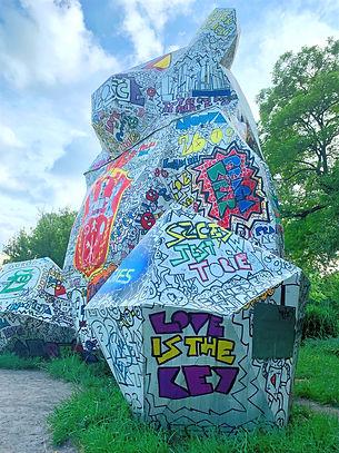 """Escultura de urso em que se lê em inglês """"Love is the Key"""" (o amor é a chave)."""