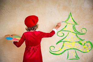 Child painting Christmas decorations. Ki