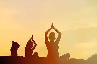 silhouette of mother and kids doing yoga