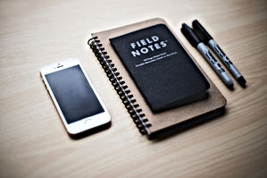 Desk with iPhone and notebook