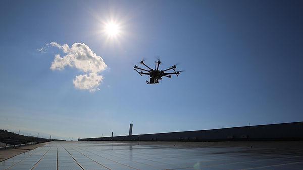 A drone flying over solar panels with the sun behind