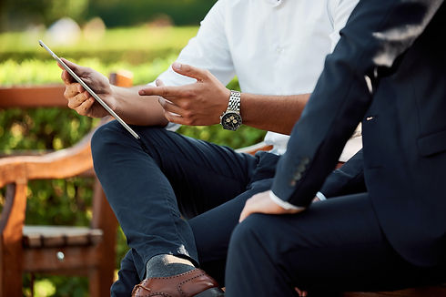 Two people sitting on a park bench looking at an iPad