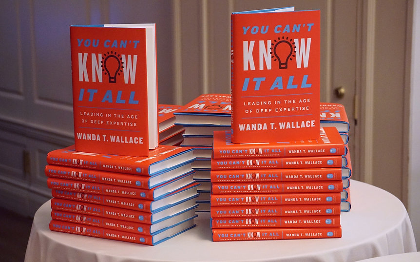 'You Can't Know It All' books stacked up on table