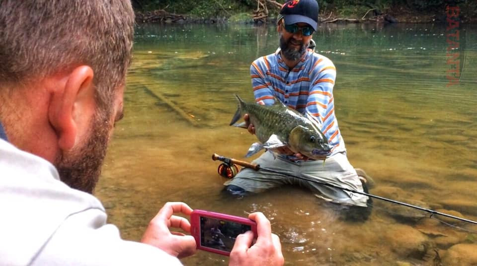 Photographer takes photo of angler with jungle stream mahseer catch