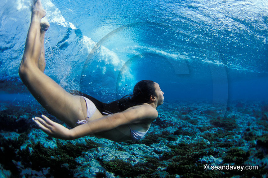 under water view of girl swimming under passing wave at Ha'atafu