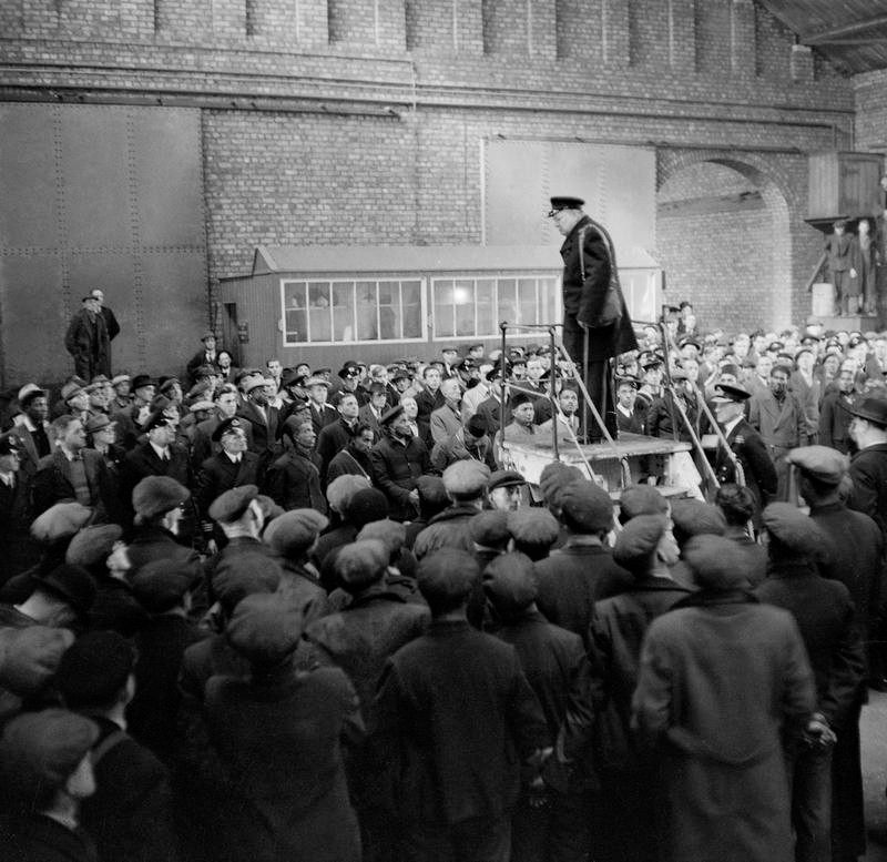 The Prime Minister, Mr Winston Churchill, making a speech (in warehouse setting) to merchant ships' crews and dockers at Liverpool, in which he thanked his listeners for their part in helping win the Battle of the Atlantic.