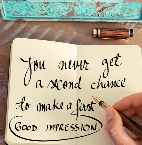 """A hand with a pen has just written the saying, """"You never get a second chance to make a first good impression."""
