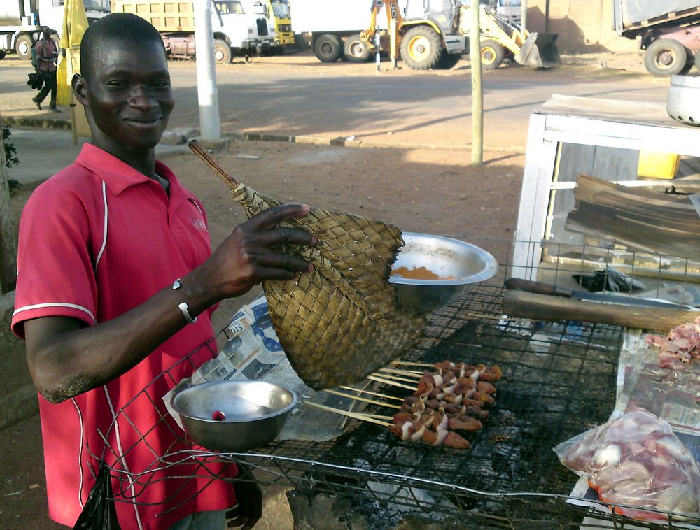 Young African man cooking wood skewers of kyinkykyinga, Ghanaian shish kebab