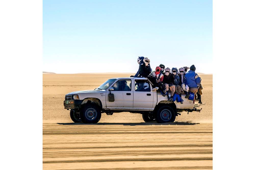 Migrants in the back of a pickup truck migrating across the Sahara desert
