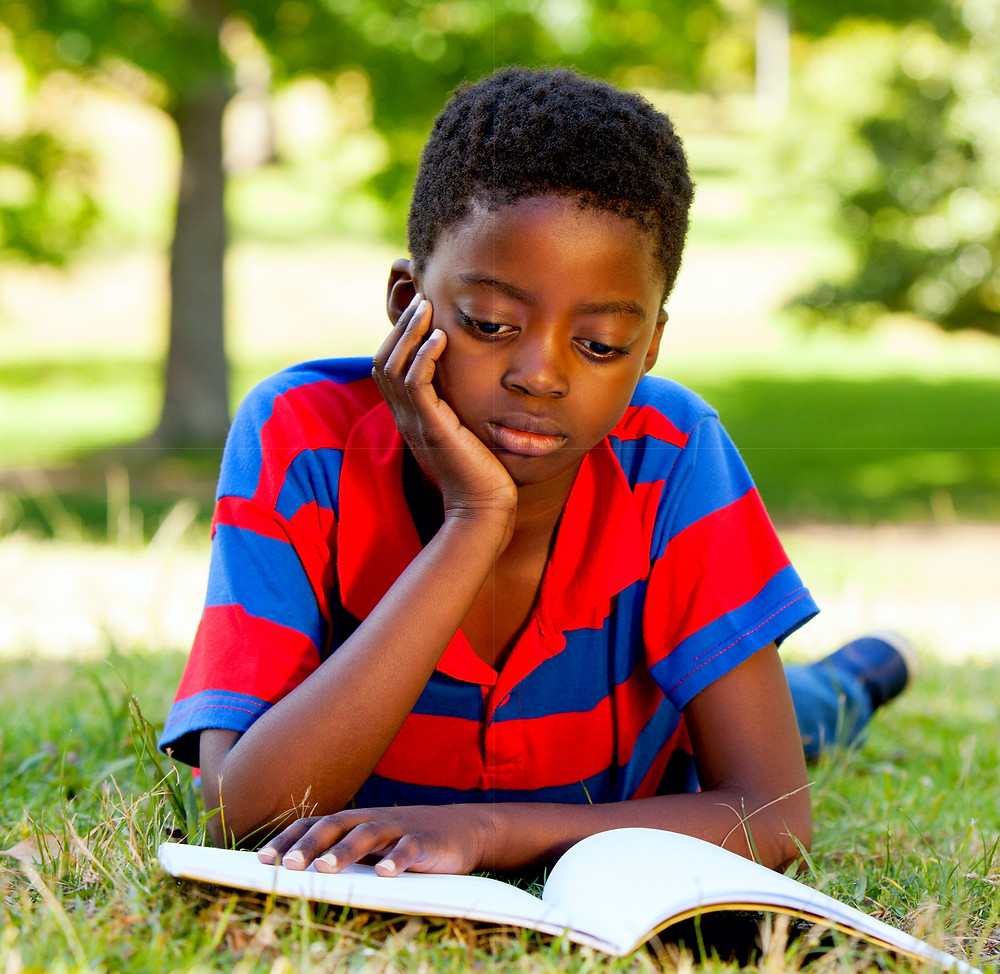 Young studious black boy reading outside
