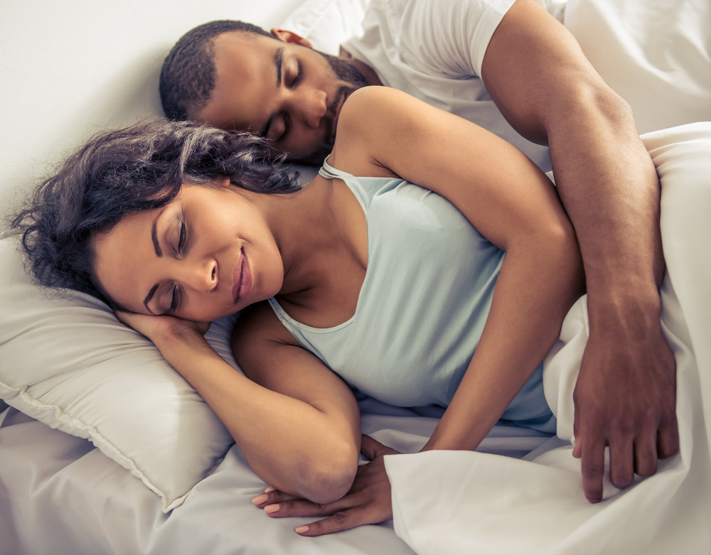 Black man in bed with black woman with his arm around her waist