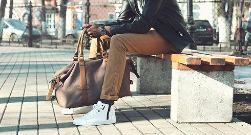 Fashion african man holding bag sitting