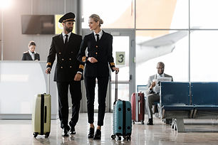 male and female pilots walking by airpor