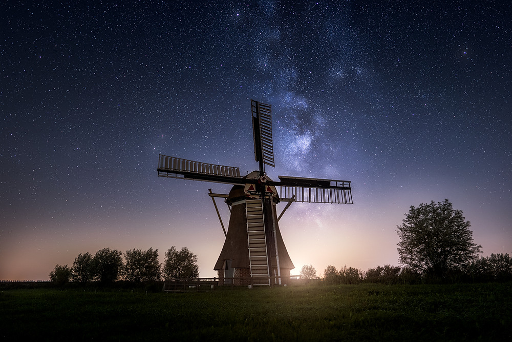 milky way above a windmill in the netherlands
