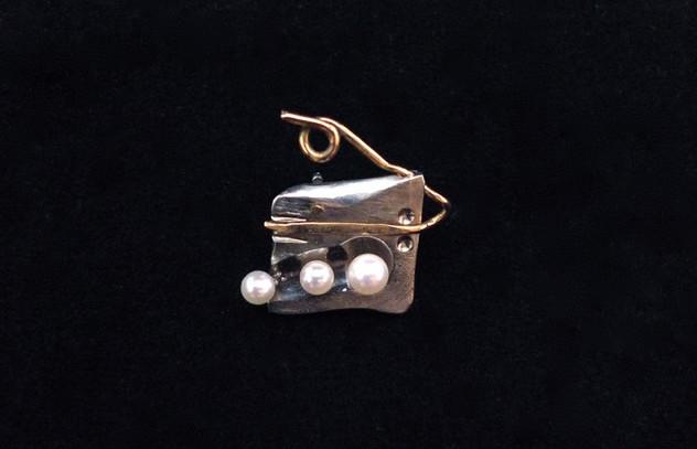 Brosch i titan med pärlor och guld